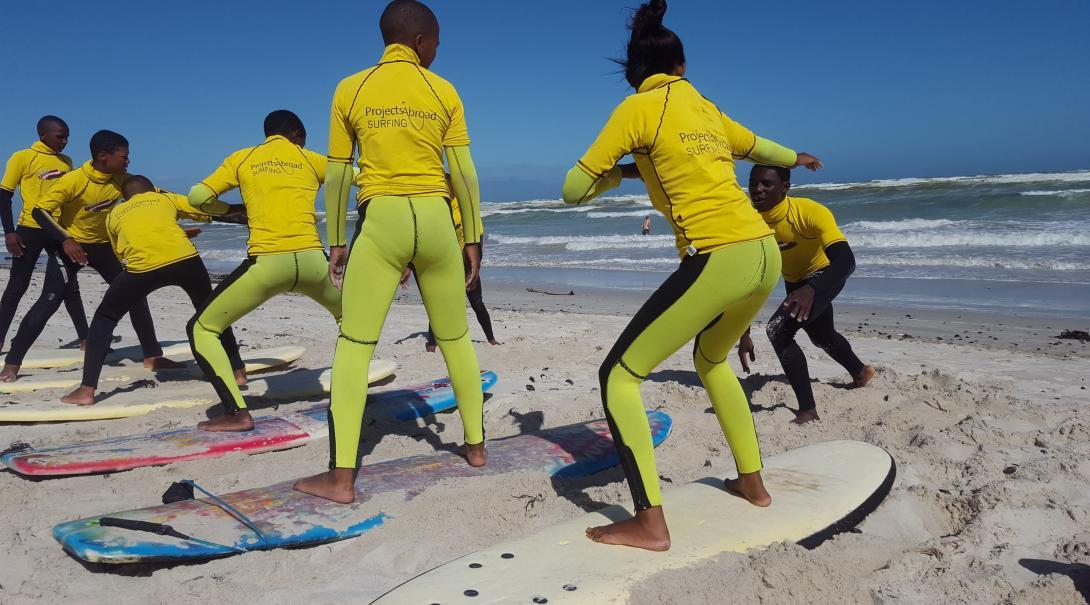 Des enfants sud-africains apprennent à se tenir sur les planches de surf de la plage de Muizenberg, guidés par un instructeur.